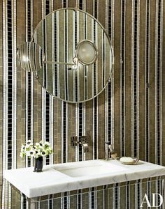 Striped wallpaper in bathroom with round mirror and small vase of flowers