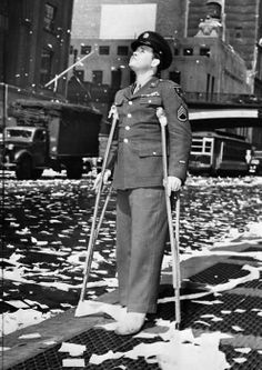 A wounded American serviceman during a ticker tape parade in New York following press reports of the unconditional surrender of Germany. May 7, 1945. [495x700] - Imgur