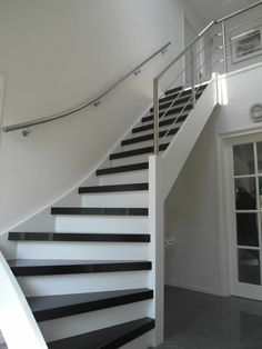 Mooie open trap met een rvs balustrade schuin op trap en een gebogen muurleuning.