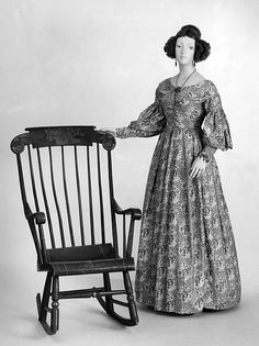 """This charismatic dress shows important features of late 1830s dress in its intriguing highly detailed small-scale textile and its low wide shoulders which enhance the bust.  Contemporaneous resources referred to the gathered treatment of the bodice as """"corsage à la Sevigné"""" or """"""""à la Maintenon"""" referencing fashionable women of the 18th-century court of Louis XIV whose much less modest décolletage the gathering imitates"""