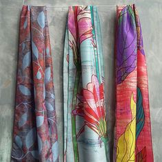 Three beautiful silk scarves made from printed silk with colourful patterns.