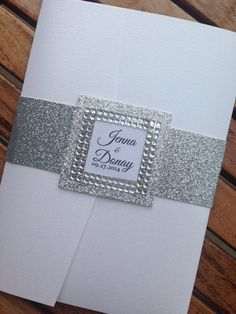 White linen and silver Glitter wedding invitation with a gems trim on monogram and inside invite.