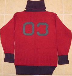 University of Pennsylvania Spalding Brand 1903 Colorful Turtleneck Football Sweater.  This is a larger sized sweater featuring heavy red wool with purple (or more likely faded navy blue) neck, wrist cuffs, and bottom areas.  The sweater features an early style Spalding tag that dates to the 1900 to 1904 range, with the tag being in the bottom area of the sweater.  Near the Spalding tag is a small sewn in tag reading Nelson.  The sweater likely was worn by C.A. Nelson.