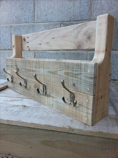 Coat rack with scarf/hat storage area. Constructed out of pallet wood pieces which have been sanded and waxed