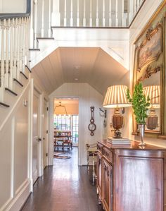 foyer with wood walls under stairs