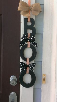 Painted wooden letters for front door hung with ribbon.