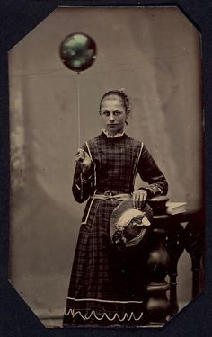 Young woman holding helium-filled balloon,  ca. 1890