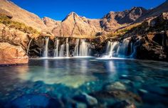 Fairy Pools, Scotland ~ What this series of waterfalls lacks in height, it makes up for in sheer, ethereal beauty. Located on the Isle of Skye at the foot of the Black Cuillin mountains, the Fairy Pools are so-named because the crystalline, blue-and-green-dappled water is so crisply beautiful it seems to defy nature. Famous Waterfalls, Beautiful Waterfalls, Places In Scotland, Fairy Pools, Largest Waterfall, Plitvice Lakes National Park, Yosemite Falls, Les Cascades, Rock Pools