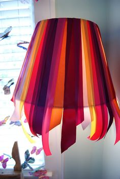 i like the way the ribbons hang off of the bottom of the lampshade. i would use cotton to do it differently though.