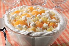 Mandarin oranges, crushed pineapple, mini marshmallows and coconut are spooned into a whipped topping-lined bowl for a divine dessert.