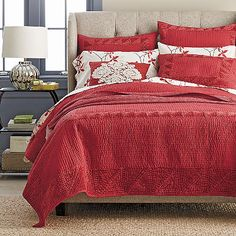 Crafted of pure cotton, this vibrant red quilt features a tonal velvet border for luxurious textural contrast.