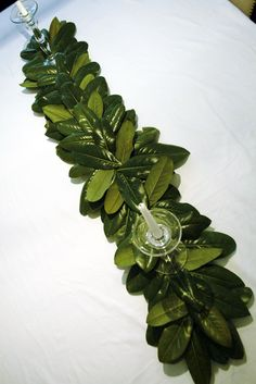 Magnolia leaf table runner...inexpensive way to decorate...add some flower heads and more candles and ur good.