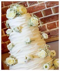 Horizontal ruffle wedding cake with fresh Flowers