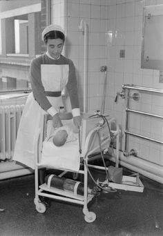 SAFETY COT DESIGNED BY NURSE AT MIDDLESEX HOSPITAL, LONDON, ENGLAND, UK, 1945  Sister Mary Williams places a young baby into the new cot she has designed at Middlesex Hospital, London. The cot is a 'box' on a stand and is leaning at a 45 degree angle: it can be laid flat. An oxygen cannister can be seen on the lower part of the frame. The ends of the cot are removable so that the baby can be treated without being lifted out.