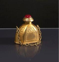 * Hôtel Meurice à Paris «Narcisse» - (années 1920) Flacon en métal doré en forme de tabatière demie sphérique à 6 pans à décor en réserves de feuilles de lierre, avec son bouchon orné d'un cabochon imitation rubis et sa chainette