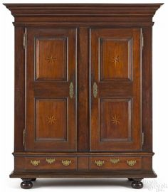 Winning bid:$15,000  Pennsylvania walnut schrank, late 18th c., with star inlaid doors, 86'' h., 65 1/2'' w. - Price Estimate: $2000 - $4000