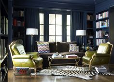 blue & lime green eclectic library office design with bold peacock blue teal glossy walls paint color, built-ins, bookshelves, chocolate brown velvet, sofa, crystal column floor, lamps, brass mirrored coffee table, French green leather chairs, white & black zebra cowhide rug, built-ins, bookshelf bookshelves and blue drapes.