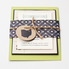 These fun, modern wedding invitations are screen printed on kraft, green, white, newsprint, and navy papers, wrapped with a retro patterned band, and tied with twine and a state-themed hang tag.