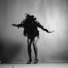 Fulllength studio portrait of American rock singer Tina Turner wearing a dark crocheted minidress while looking down and stretching her arms out to...