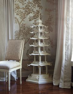 "A four-foot-high pagoda in the dining room of a Brookville, New York, house ""is just here to make people smile,"" says designer Andrew Raquet. The silver tea-leaf wallpaper is from Gracie."