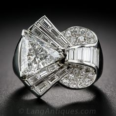 This uniquely fabulous vintage diamond ring explodes in a blaze of bright white diamonds centering on a faceted triangle, or trilliant, cut diamond weighing 2.10 carats. The artfully sculpted, multi-dimensional mounting, rendered in platinum, combines baguette and round diamonds for a brilliant effect. We estimate the vintage of this platinum ring to be from the 1930s through the 1950s due to the trilliant cut diamond, and may be one of the earliest examples of jewelry to utilize this modern…