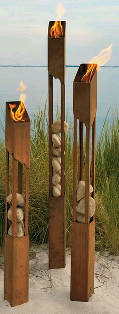 Tiki Torches flame lights for path way side walk made out of rusty metal. Instead of rocks in the tiki torches I would like old Metal Gears (second picture). Landscape Lighting, Outdoor Lighting, Outdoor Decor, Lighting Ideas, Lighting Design, Lighting Solutions, Outdoor Fire, Backyard Lighting, Rustic Outdoor