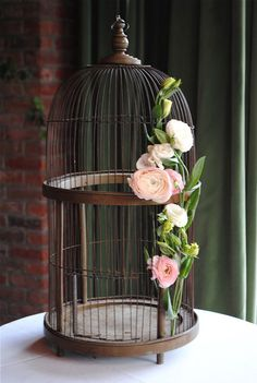 large vintage birdcage with pink ranunculus for cards at wedding
