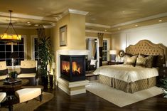 A large master bedroom with an open concept space offering a roaring fire, a sitting area, and ample pot lighting.