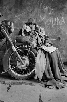 Poor woman sitting in front of a motorcycle 1966
