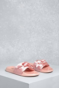 A pair of slides by LFL by Lust for Life™ featuring a lightweight feel and a satin bow upper design.
