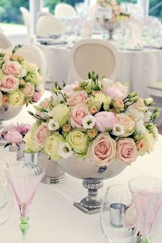White table setting with pale pink and green glass and matching flowers in silver.