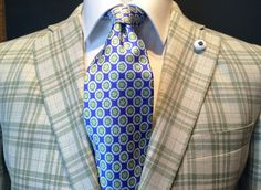 Soft plaid pattern in a warm off-white and olive palette with a subtle pink accent. Paired with a silk lined tie in a geometric medallion pattern. The scale of the tie and the plaid compliment each other nicely, and the contrast of the high sheen tie and matte weave of the jacket are very striking.