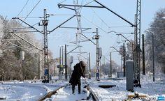 POLAND, Popielarze: A woman clears the rails from snow after first heavy snow fall in Popielarze village near Warsaw on December 26, 2014. AFP PHOTO/JANEK SKARZYNSKI