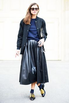 Virginie Muys in a black bomber jacket + navy blue sweater + black pleated leather midi skirt + black oxfords