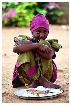 A hausa girl dressed in Green and purple in a small village of northern Nigeria, photograph by Gianluca Di Santo