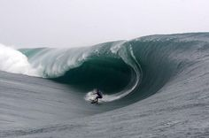 SPORTS DANGERS - INCREDIBLE SURFER SHOT AS HUGE WAVE SURGES AND BEGINS TO CURL OVER TOP - 30 FEET UP!