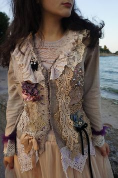 Romantic baroque inspired feminine jacket. The jacket is hand dyed in very beautiful tea colour and beige, its adorned with variety of antique and vintage laces and tulles, hand sculpted flowers, very beautiful vintage beaded pieces. The jacket is in victorian style, very elegant and beautiful piece, its decorated with crystals, pearls and beading. Perfect for evening occasions or weddings. The jacket fastens with lace ribbons in the back. Hand beaded piece of unique. Measurements: Size M…