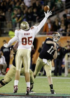 Notre Dame quarterback Tommy Rees (11) throws a pass over the arm of Florida State defensive end Bjoern Werner (95) during the second half of the Champs Sports Bowl NCAA college football game, Thursday, Dec. 29, 2011, in Orlando, Fla. Florida State won 18-14. (AP Photo/John Raoux)