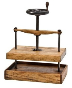 """Old american industrial screw press with a centrally located iron screw shaft retaining the original wheel with tapered wood handle. the varnished oak wood press works by using the coarse screw to convert the rotation of the handle or """"drive-wheel"""" into a small downward movement of greater force. the overhead handle did not contain flyweights. the unique vintage industrial press remains in excellent working condition. measures 15 1/2 x 10 3/4 x 18 inches."""
