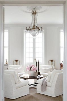 french style living room with white linen slip covers on four arm chairs, white walls, sisal rug, dark wooden round coffee table