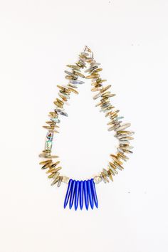 Rodeo Road Necklace: this labradorite tusk stone necklace features 2 raw unpolished pyrite beads on either side of 7 large blue magnesite beads in the center with abalone shell on the side for an asymmetrical pop of color.