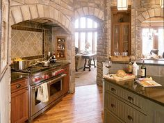 The gas range has an alcove of its own surrounded by cultured stone. Narrow, built-in shelves on either side of the range                             are perfect for storing spices.