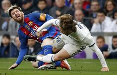 Lionel Messi cries out in pain as Real Madrid midfielder Luka Modric sends him sprawling with a biting challenge