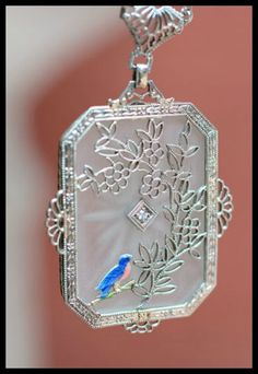 Detail view of an antique Art Deco camphor glass and filigree pendant with an unusual enameled bird detail and classic paperclip chain
