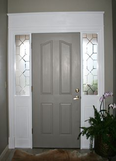 Fix the front door--add wooden panels to the bottom of the long windows, paint and molding