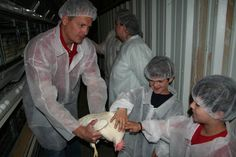 Clint Hickman of Hickman's Family Farms shows two young aspiring farmers how to lovingly handle a laying hen. Hickman's chicks are lovely ladies and know how to produce wonderfully delicious eggs for thousands of Arizona families!