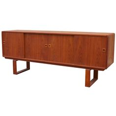 Danish teak sideboard with sliding doors and continuous legs. 1960s