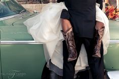 Country bride and groom stealing a kiss on a broken down car. Cowboy boot bride