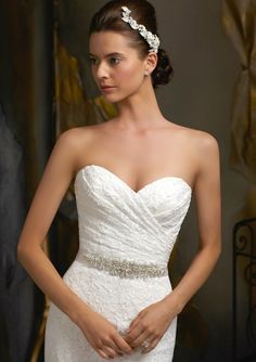 Hearts will flutter when you walk down the aisle in the stunning Amelia Grace.  The charming sweetheart neckline is crafted with a french heirloom romantic lace.  Show off that sleek waistline with a beaded crystal sash and corset back with detachable ribbon. - http://TheChicFind.com