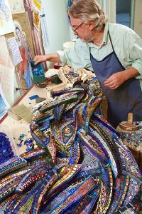 Giulio Menossi at work on small mosaic panels.